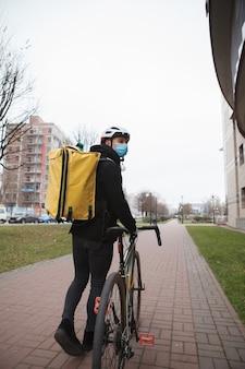 Courier com máscara médica, carregando mochila térmica, caminhando pela cidade de bicicleta