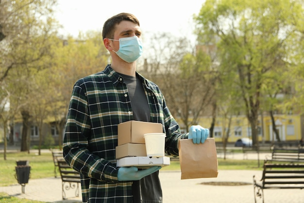 Courier com máscara protetora e luvas médicas entrega comida para viagem