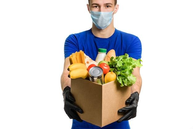 Courier com uma máscara médica segura uma caixa de papelão com comida, isolada em um fundo branco.