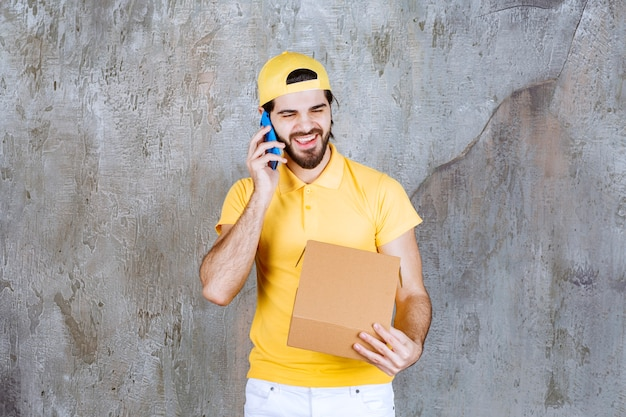 Courier de uniforme amarelo segurando uma caixa de papelão aberta e recebendo pedidos por telefone