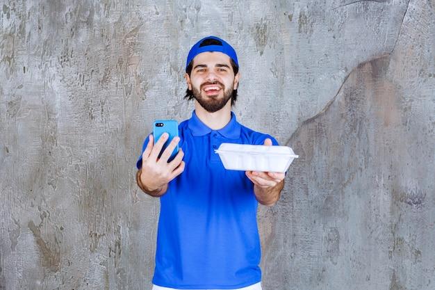 Courier de uniforme azul segurando uma caixa de plástico para viagem e recebendo novos pedidos por telefone.