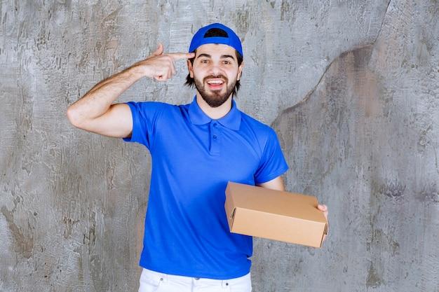 Courier de uniforme azul segurando uma caixa para levar e parece confuso ou tendo uma nova ideia.