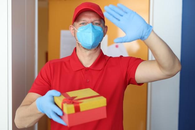 Courier em luvas e máscara médica protetora tem uma caixa de presente nas mãos.