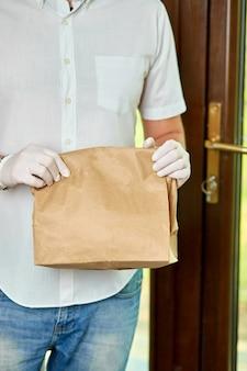 Courier entrega compras on-line à porta durante a epidemia de coronavírus