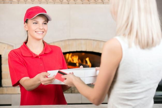 Courier entrega pizza ao cliente.