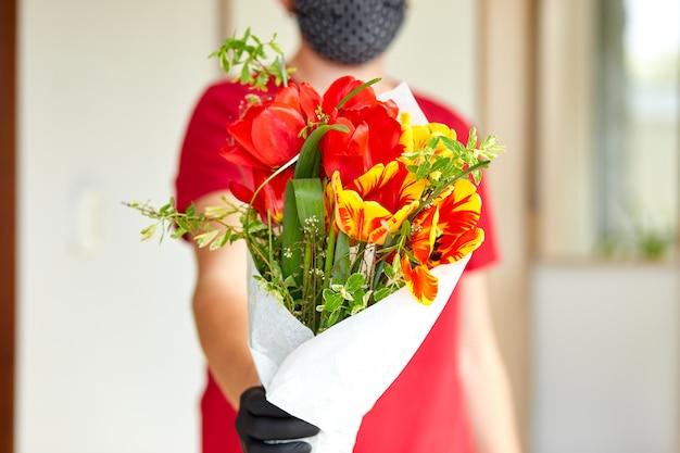 Courier, entregador de luvas médicas de látex entrega com segurança as compras on-line de um buquê de flores