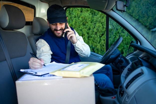 Courier falando ao telefone sobre a entrega dos pacotes.