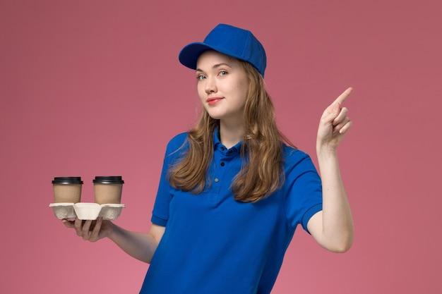 Courier feminina de uniforme azul segurando xícaras de café marrons com um leve sorriso no uniforme de serviço de fundo rosa entregando trabalho da empresa