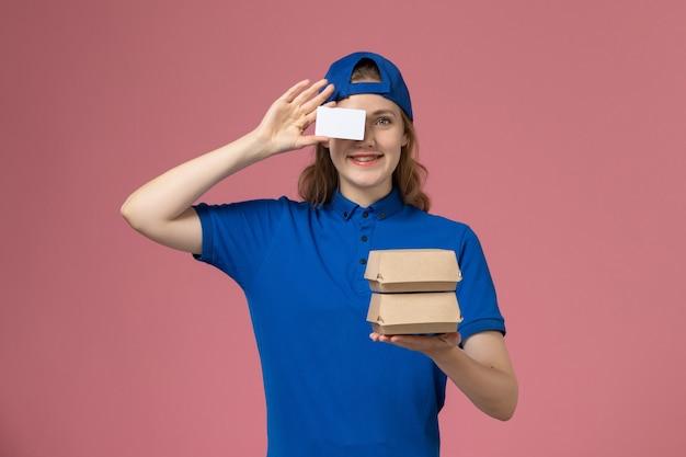 Courier feminino de frente para a capa uniforme azul segurando pequenos pacotes de comida para entrega e um cartão no fundo rosa.