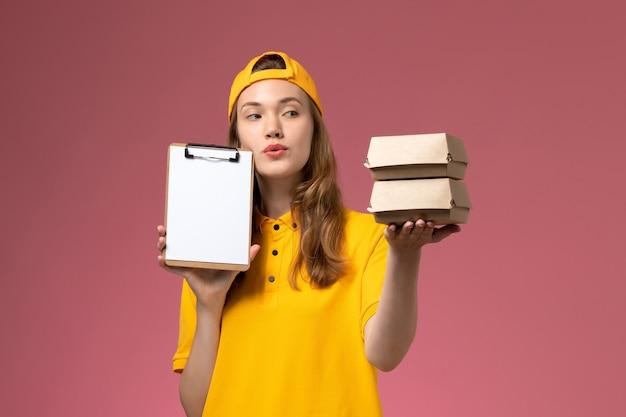 Courier feminino de frente para o uniforme amarelo e capa segurando pequenos pacotes de comida para entrega com bloco de notas na parede rosa.
