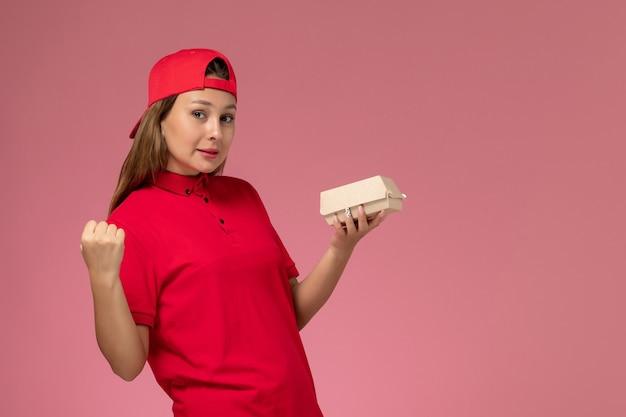 Courier feminino de frente para o uniforme vermelho e capa segurando o pacote de entrega de comida no fundo rosa uniforme entrega serviço empresa trabalho trabalhador