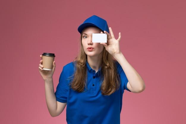 Courier feminino de uniforme azul segurando uma xícara de café marrom com cartão branco na mesa rosa claro.