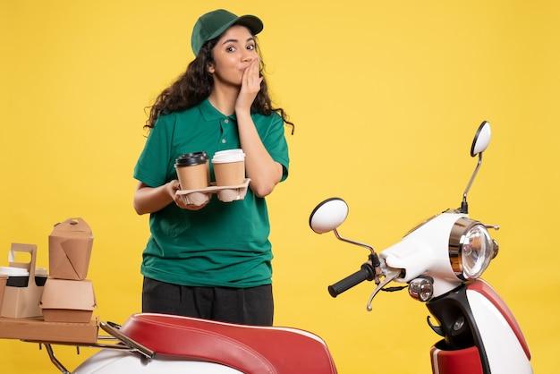 Courier feminino de uniforme verde com café em cor de fundo amarelo entregador de trabalho trabalhador de serviço de alimentação de frente