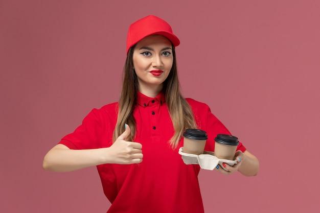 Courier feminino de uniforme vermelho segurando xícaras de café marrom no fundo rosa claro serviço entrega uniforme trabalhador trabalho feminino empresa