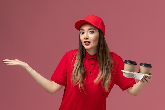 Courier feminino de uniforme vermelho segurando xícaras de café marrom no fundo rosa serviço de entrega uniforme trabalhador trabalho feminino empresa