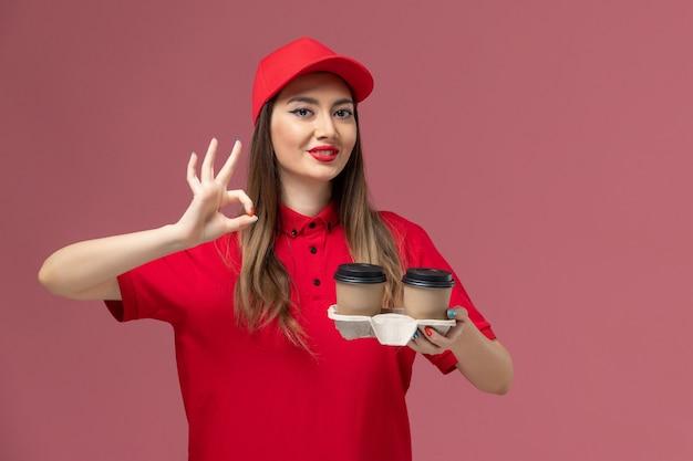 Courier feminino de uniforme vermelho segurando xícaras de café marrons sorrindo sobre fundo rosa claro serviço entrega uniforme trabalhador trabalho feminino empresa