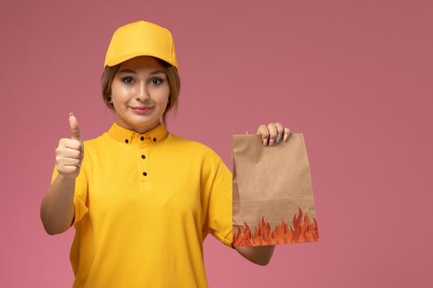 Courier feminino de vista frontal com capa amarela uniforme amarela segurando pacote de comida e mostrando como sinal no fundo rosa uniforme entrega trabalho cor trabalho