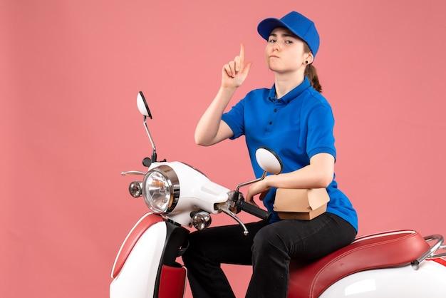 Courier feminino de vista frontal com pequeno pacote de comida na bicicleta de entrega de comida de trabalhador de cores rosa uniforme.