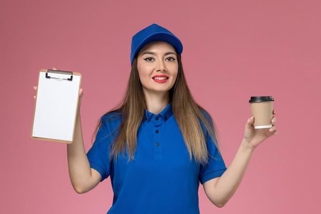 Courier feminino de vista frontal com uniforme azul e capa segurando a xícara de café de entrega e o bloco de notas na parede rosa trabalhador