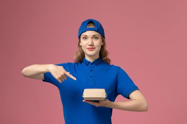 Courier feminino de vista frontal com uniforme azul e capa segurando um pequeno pacote de entrega de comida no fundo rosa.