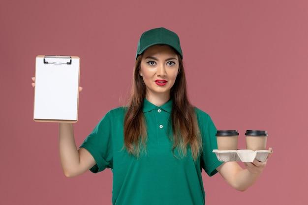 Courier feminino de vista frontal com uniforme verde e capa segurando xícaras de café de entrega e bloco de notas na parede rosa.