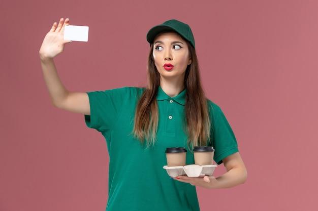 Courier feminino de vista frontal com uniforme verde e capa segurando xícaras de café de entrega e cartão na parede rosa serviço de trabalho uniforme trabalhador de entrega