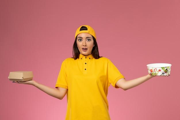 Courier feminino de vista frontal em uniforme amarelo e capa segurando o pacote de comida com a tigela na parede rosa claro.