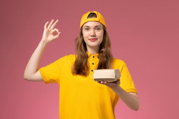 Courier feminino de vista frontal em uniforme amarelo e capa segurando pacote de entrega de comida na parede rosa uniforme de serviço de entrega de empresa trabalhador