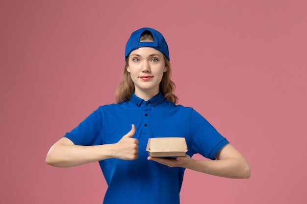 Courier feminino de vista frontal em uniforme azul e capa segurando um pequeno pacote de entrega de comida no fundo rosa uniforme de entrega empresa trabalho menina trabalho