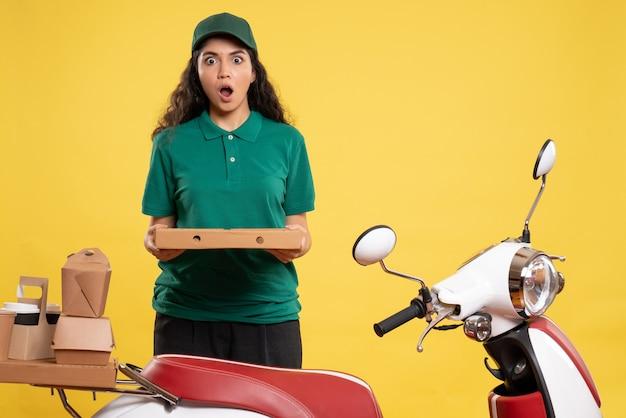 Courier feminino de vista frontal em uniforme verde com caixa de pizza em fundo amarelo.