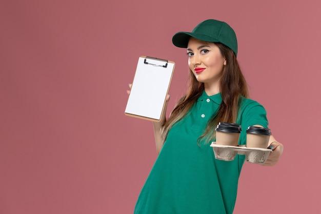 Courier feminino de vista frontal em uniforme verde e capa segurando o bloco de notas e copos de café de entrega na mesa rosa serviço uniforme trabalho de entrega