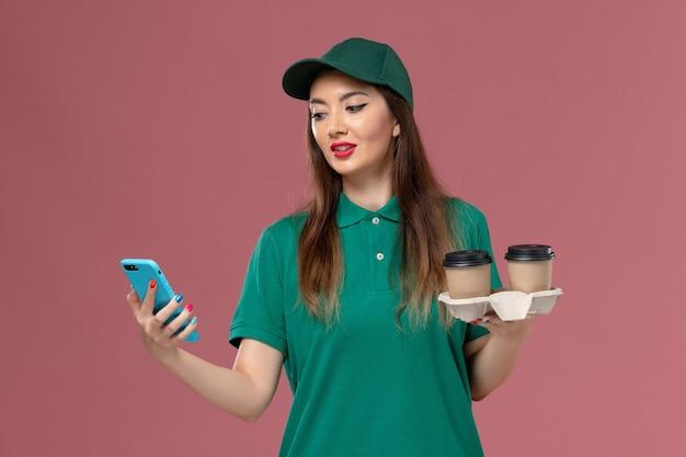 Courier feminino de vista frontal em uniforme verde e capa segurando xícaras de café de entrega e telefone na parede rosa serviço de entrega uniforme de trabalho