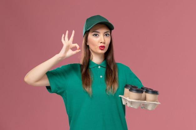 Courier feminino de vista frontal em uniforme verde e capa segurando xícaras de café de entrega na mesa rosa claro.