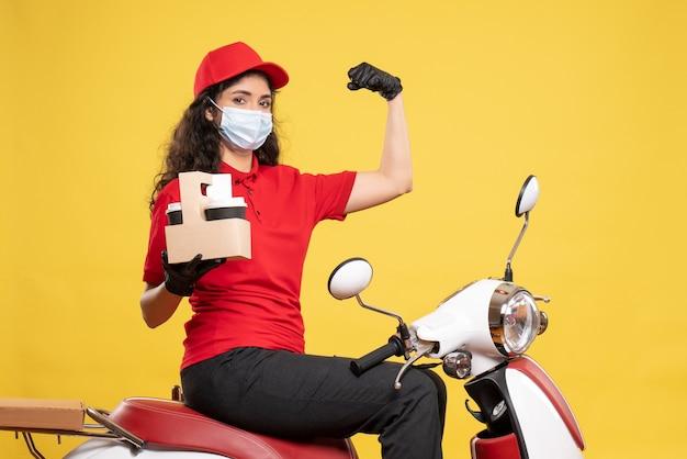 Courier feminino de vista frontal máscara com xícaras de café em fundo amarelo covid - pandemia de serviço de trabalhador uniforme de entrega de trabalho