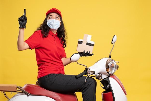 Courier feminino de vista frontal máscara com xícaras de café em fundo amarelo covid - trabalhador uniforme de entrega de trabalho