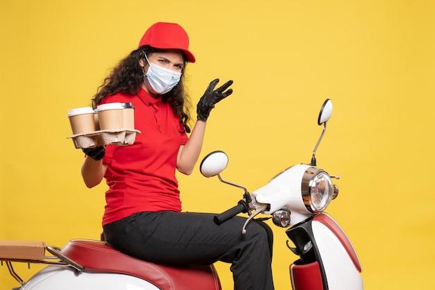 Courier feminino de vista frontal máscara com xícaras de café em fundo amarelo pandemia de trabalhador uniforme entrega covid-job