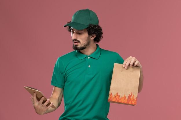 Courier masculino de frente para o uniforme verde e capa segurando o bloco de notas e o pacote de comida no fundo rosa.