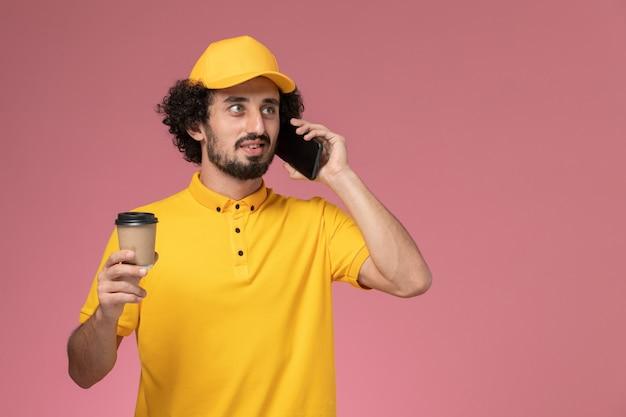 Courier masculino de uniforme amarelo e capa segurando a xícara de café de entrega e o telefone na parede rosa