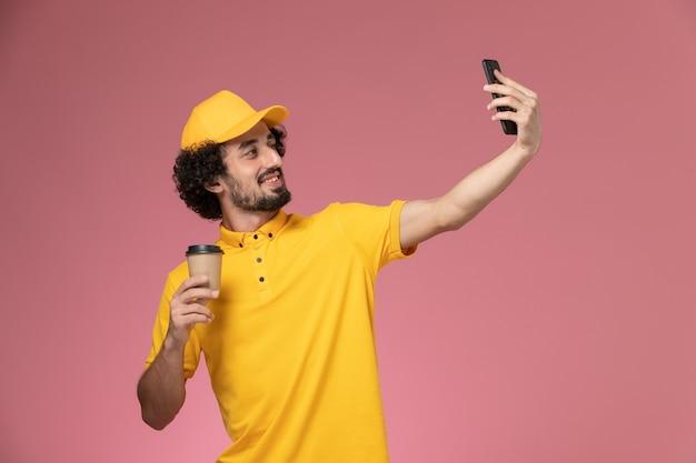 Courier masculino de uniforme amarelo e capa segurando a xícara de café de entrega e tirando selfie na parede rosa