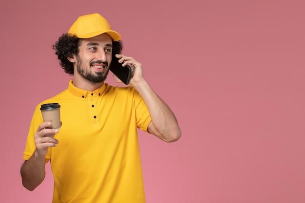 Courier masculino de uniforme amarelo e capa segurando a xícara de café de entrega falando ao telefone na parede rosa