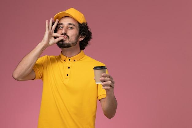 Courier masculino de uniforme amarelo e capa segurando a xícara de café de entrega na parede rosa