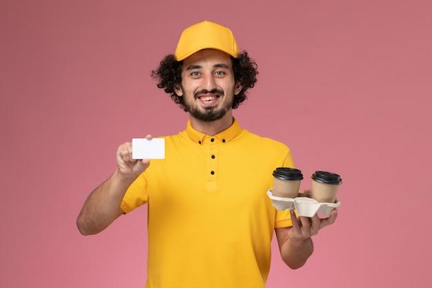 Courier masculino de uniforme amarelo e capa segurando xícaras de café marrons e cartão na parede rosa