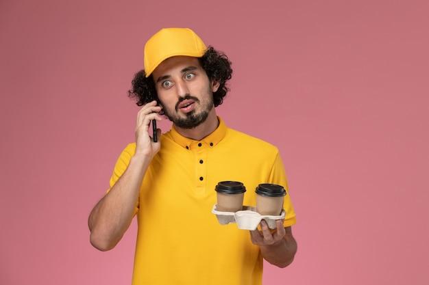 Courier masculino de uniforme amarelo e capa segurando xícaras de café marrons e falando ao telefone na parede rosa