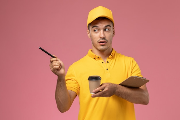 Courier masculino de uniforme amarelo segurando a xícara de café de entrega e o bloco de notas escrevendo notas na mesa rosa claro