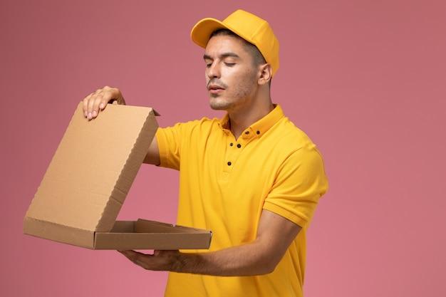 Courier masculino de uniforme amarelo segurando e abrindo a caixa de entrega de comida em fundo rosa