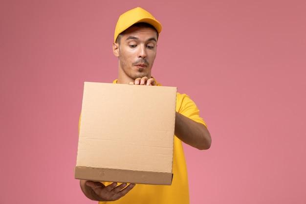 Courier masculino de uniforme amarelo segurando e abrindo a caixa de entrega de comida na mesa rosa