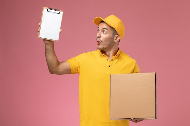 Courier masculino de uniforme amarelo segurando um bloco de notas e uma caixa de entrega de comida no fundo rosa