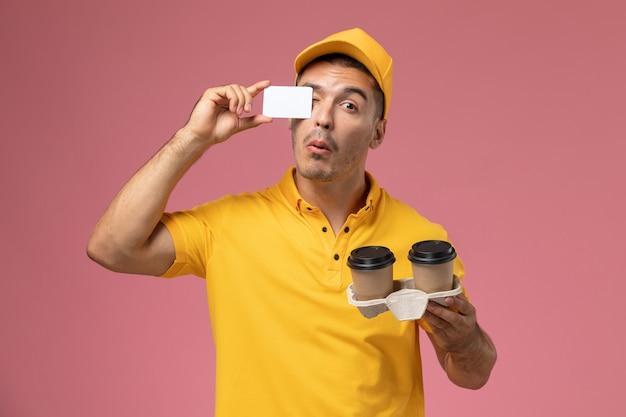 Courier masculino de uniforme amarelo segurando um cartão cinza e entregando xícaras de café em fundo rosa