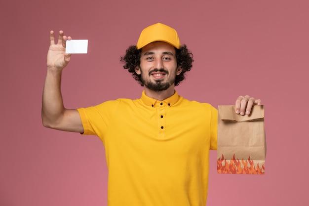 Courier masculino de uniforme amarelo segurando um pacote de comida e um cartão de plástico na parede rosa