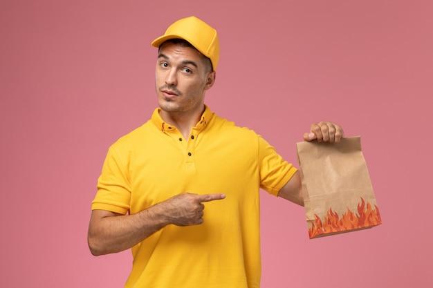 Courier masculino de uniforme amarelo segurando um pacote de comida em fundo rosa